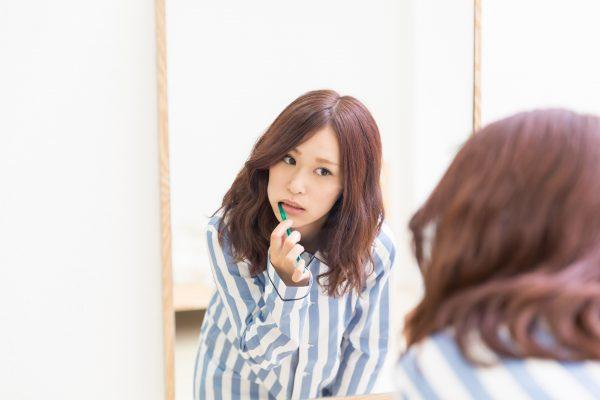 鏡の前で歯みがきをする女性