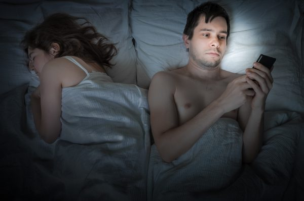 Young man is lying with girlfriend in bed and texting with phone