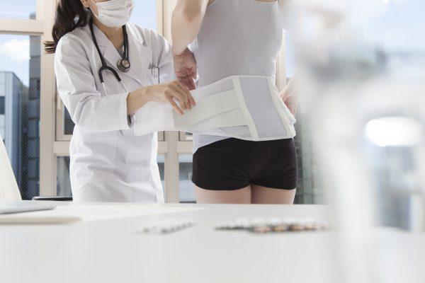 病院でコルセットを巻かれる患者